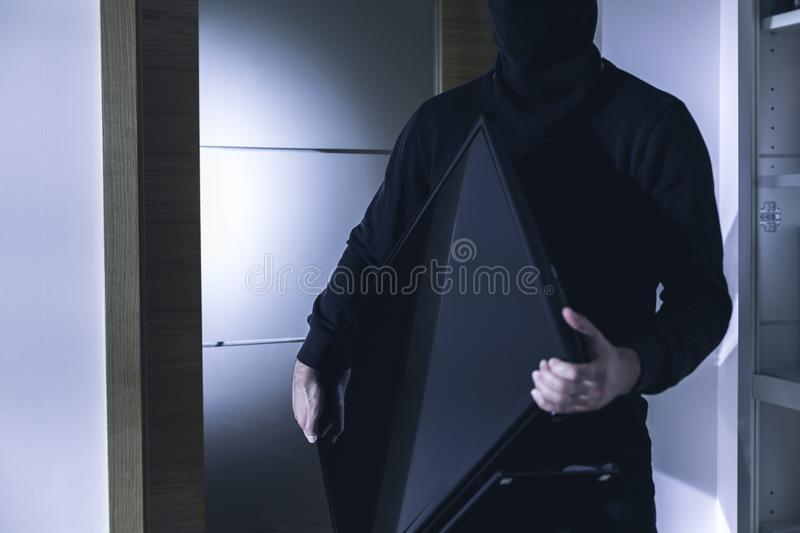 Thief holding modern expensive television royalty free stock images