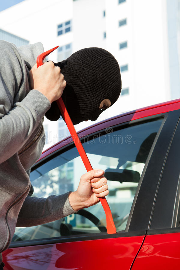 Thief in hooded jacket and balaclava opening car's door royalty free stock image