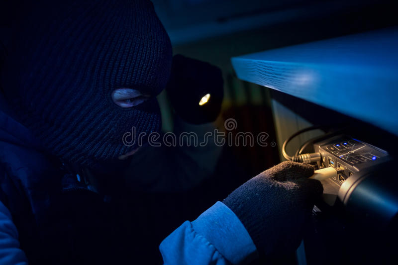 Thief inserting usb flash memory into computer stock image