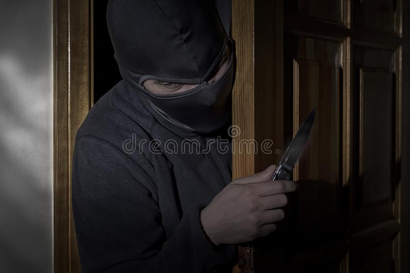 Thief with a knife in his hand and a hat with a slit for the eyes sneaks into the house through the door at night royalty free stock images
