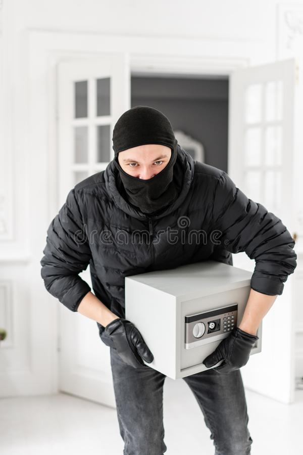 Thief looking at the camera with black balaclava stealing modern Electronic safe box. The burglar commits a crime in royalty free stock image