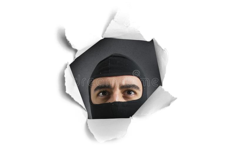 Thief looking through a paper hole stock photos