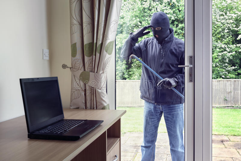 Thief looking through patio doors window at a laptop computer to royalty free stock images