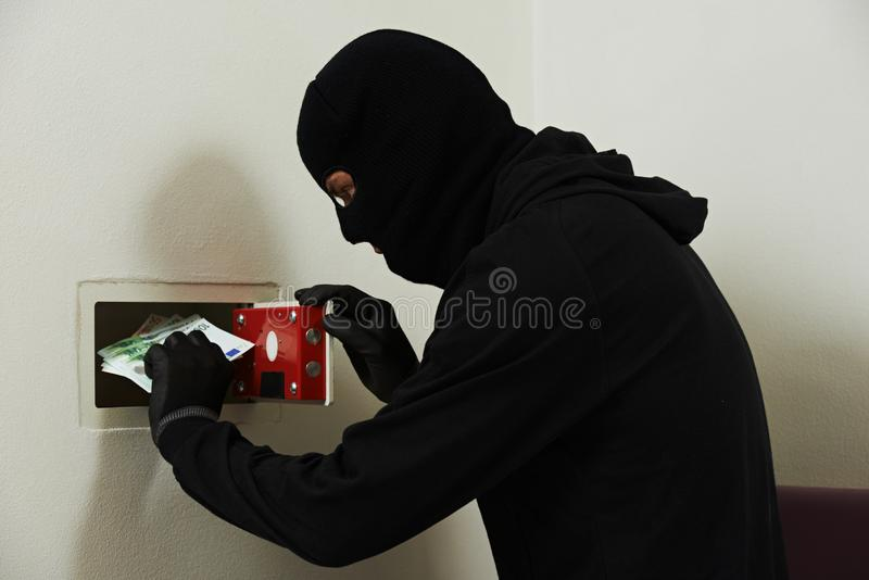 Thief in mask during safe codebreaking stock images