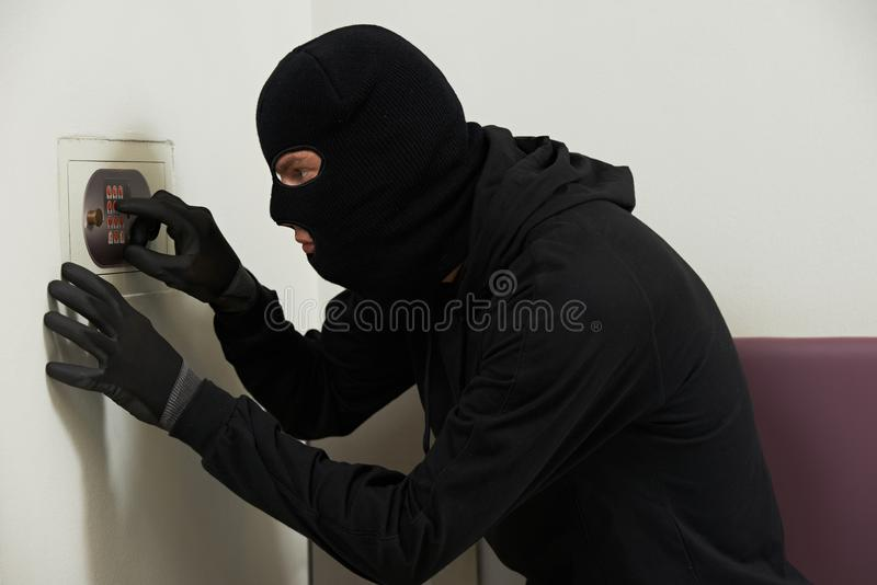 Thief in mask during safe codebreaking stock photos
