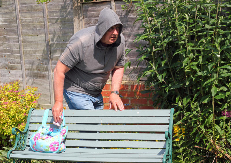 Thief or robber stealing from a handbag. A thief or robber taking the opportunity to steal from an untended bag on a bench stock photos