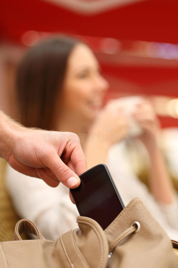 Thief stealing a mobile phone from a woman bag stock image