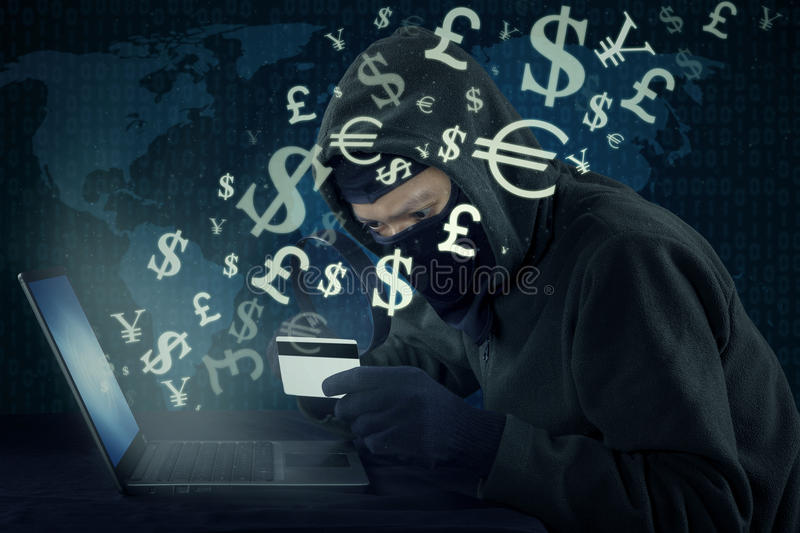 Thief stealing money with laptop and credit card. Male hacker wearing mask and using laptop to steal money with credit card and online transaction royalty free stock photos