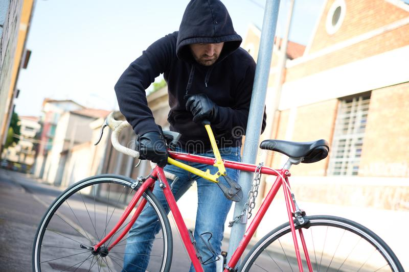 Thief stealing a bike in the city street royalty free stock photography