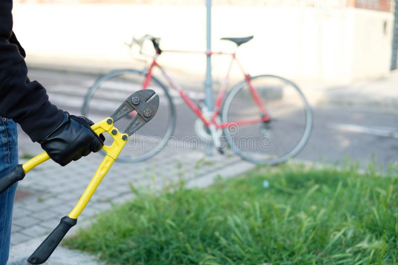Thief stealing parked bike in the city street stock photography