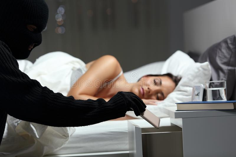 Thief stealing a phone in a bedroom stock images