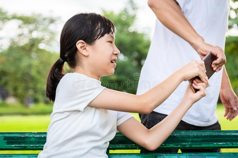 Thief stealing a smart phone to a little asian child girl sitting on a bench,bad man pulling a phone while playing,watching,chat royalty free stock photos