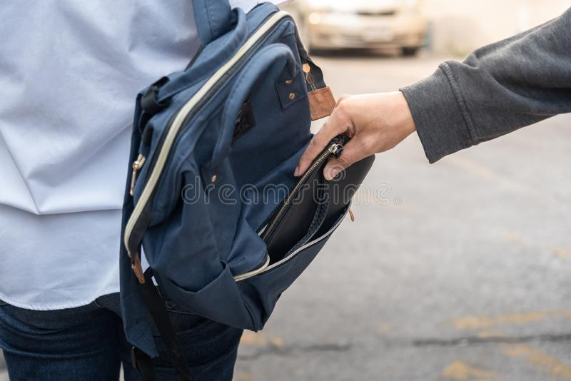 Thief stealing the wallet or mobile phone from behind young caucasian woman bag on street, thief, crime, robber and steal concept. Thief stealing the wallet or royalty free stock photo