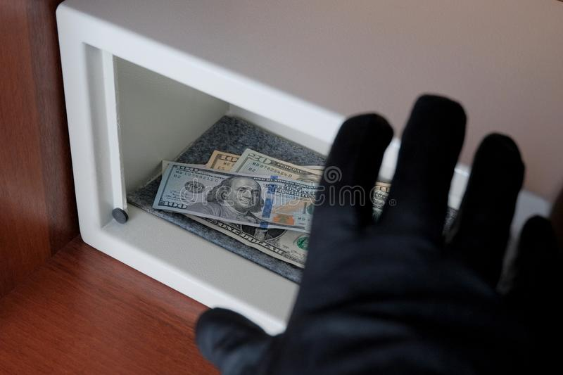 The thief steals dollar bills from a safe with a combination lock. Unreliable protection. A black-gloved hand reaches for money. stock image
