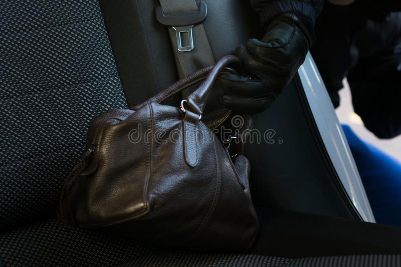 Thief steals a woman's brown bag from the rear of a car royalty free stock photos