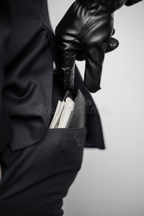 A thief takes a wallet with a cash from a pocket of a man in a s royalty free stock image