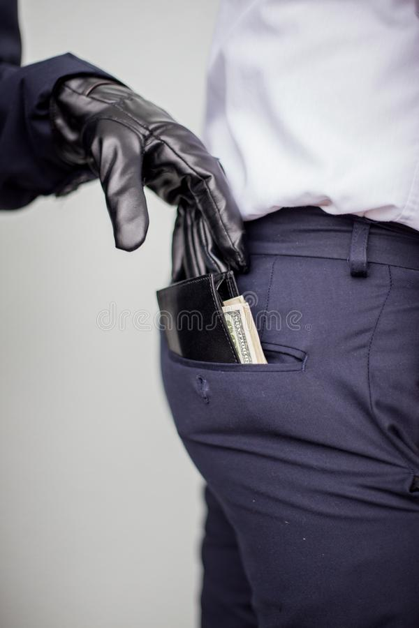 A thief takes a wallet with a cash from a pocket of a man in a s stock photos