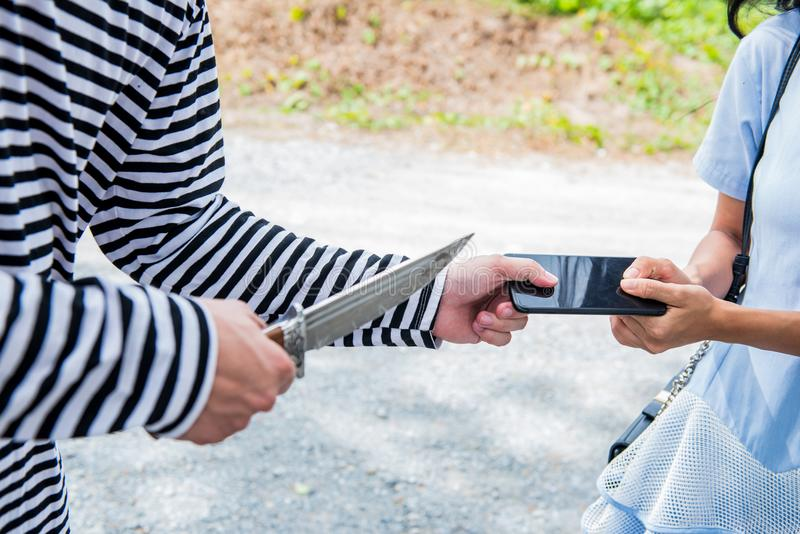 Thief is trying to steal. Mobile phone at the public place royalty free stock image