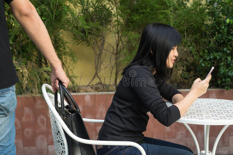Thief trying to steal and walk away the shoulder bag while woman. Using mobile phone and sitting on chair stock images