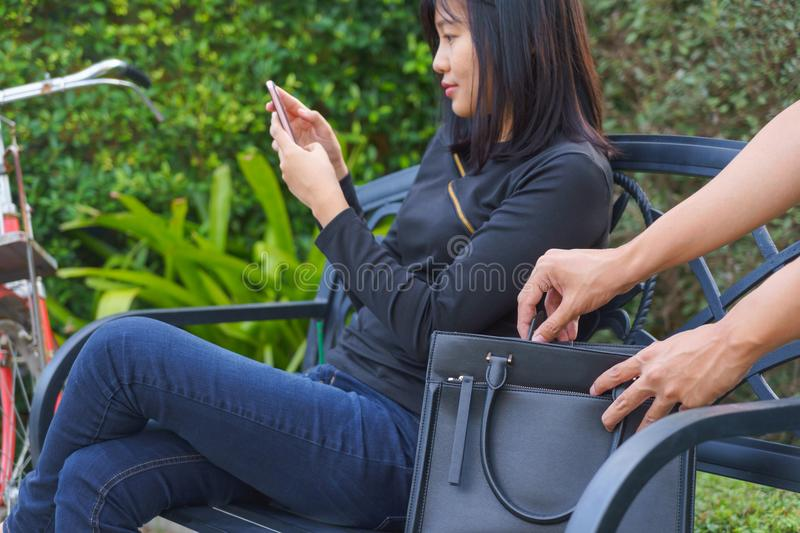 Thief trying to steal and walk away the shoulder bag while woman. Using mobile phone and sitting on chair stock photo