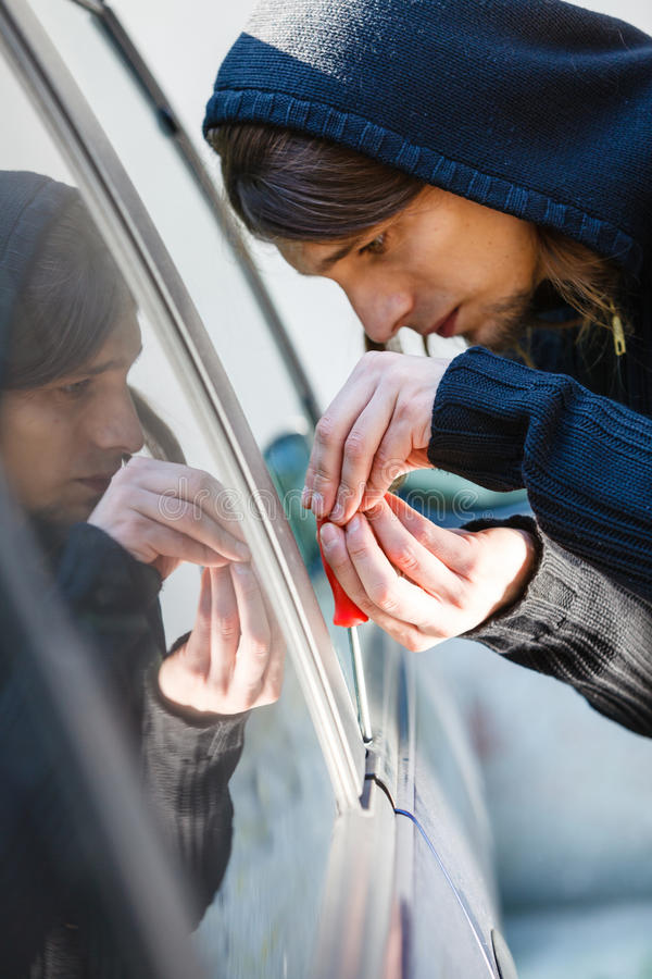 Thieft man holding screwdriver breaking into car royalty free stock image