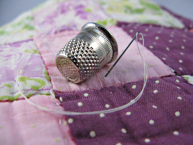 Thimble, Needle and Quilt stock image