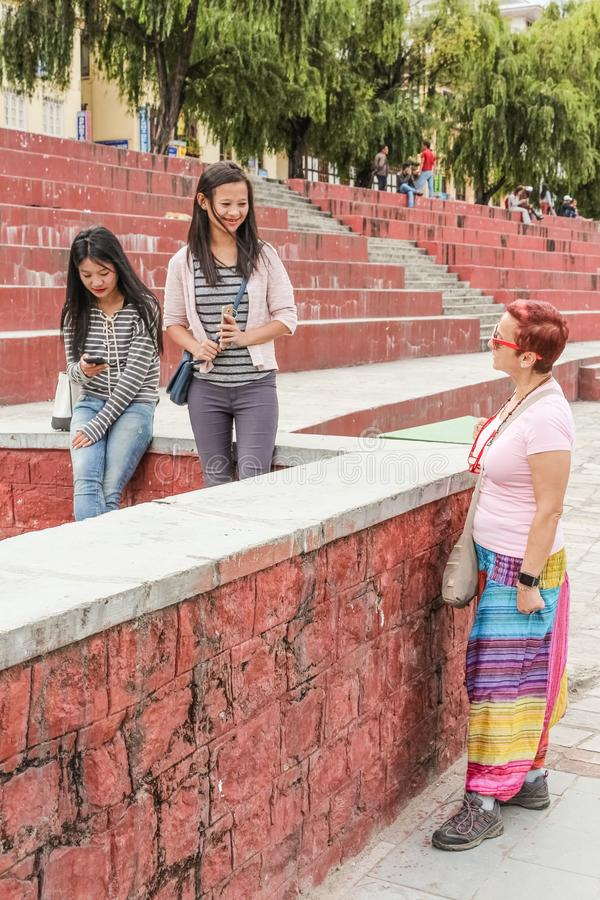 Thimphu, Bhutan - September 11, 2016: Caucasian tourist talking with locals near an amphitheatre in Thimphu, Bhutan. stock photo