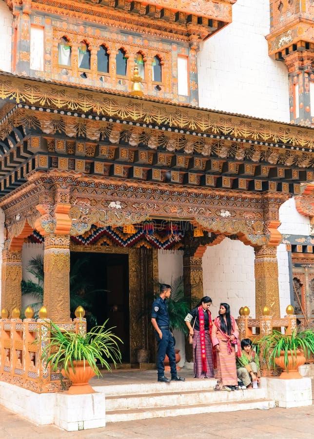 Thimphu, Bhutan - 10 settembre 2016: Guardia di palazzo reale del Bhutanese con le donne locali che stanno all'entrata della cost fotografia stock