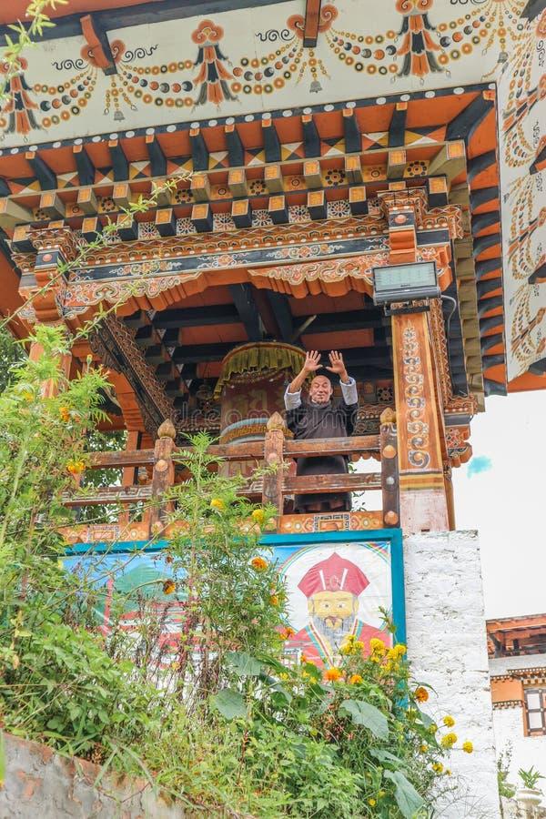 Thimphu, Bhutan - 15 settembre 2016: Il punto di vista di angolo basso di un monaco felice davanti alla preghiera spinge dentro S immagini stock