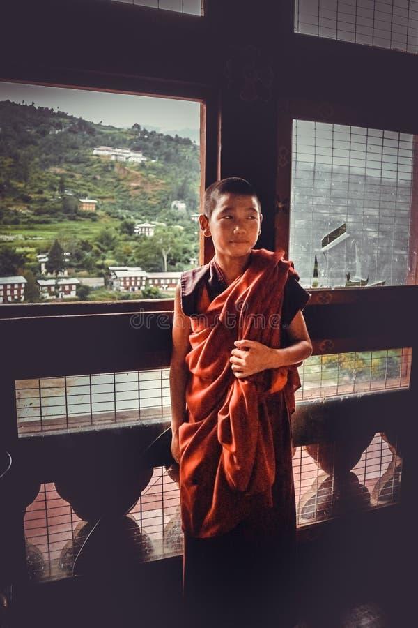Thimphu, Butão - 10 de setembro de 2016: Monge budista do principiante novo nas vestes da laranja avermelhada que estão na frente fotos de stock royalty free