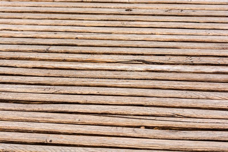 Thin brown wooden slats background. Parallel lines. Blurred background. Cracks and scuffs on the boards.  stock photo