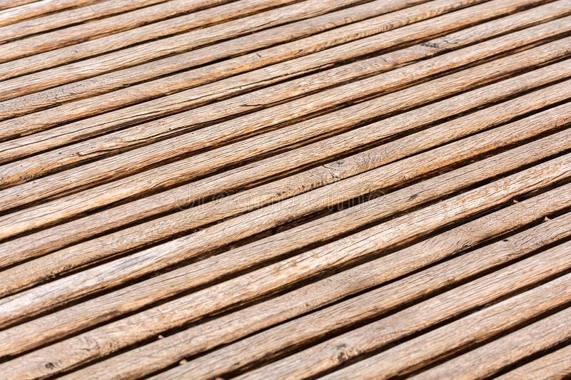 Thin brown wooden slats background. Parallel lines. Blurred background. Cracks and scuffs on the boards.  royalty free stock images