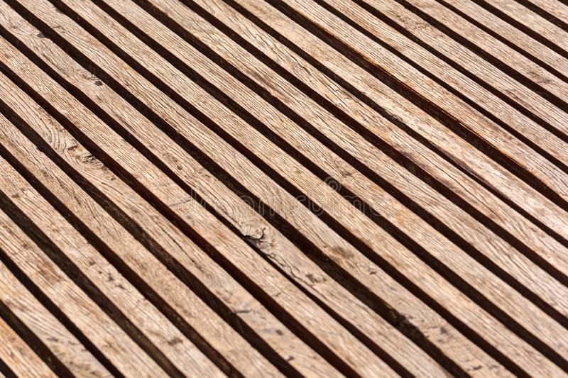 Thin brown wooden slats background. Parallel lines. Blurred background. Cracks and scuffs on the boards.  royalty free stock photos