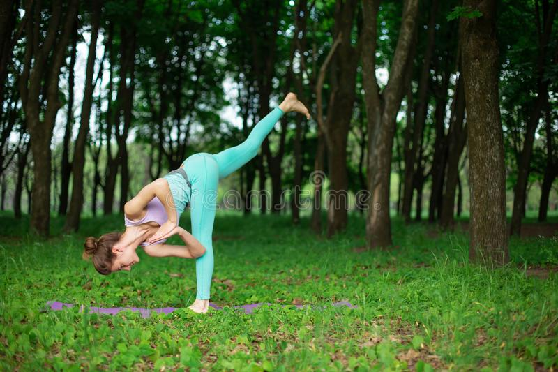 Thin brunette girl plays sports and performs beautiful and sophisticated yoga poses in a summer park. Green lush forest on the royalty free stock images