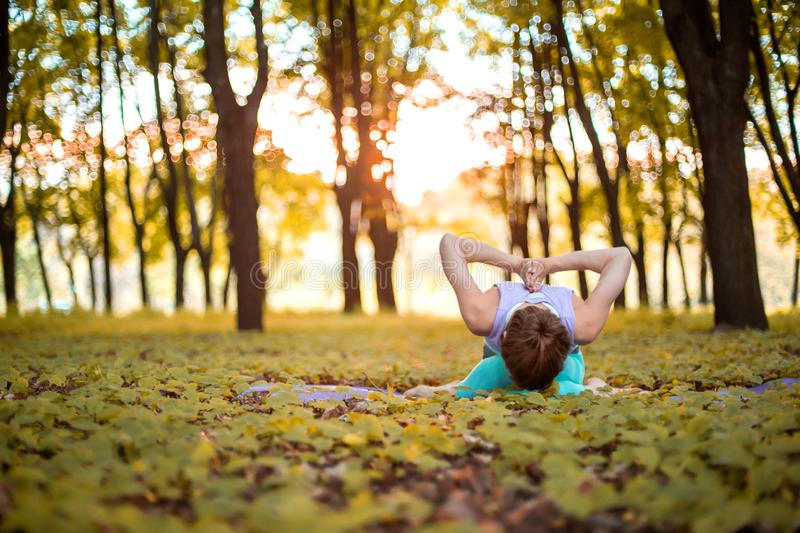 Thin brunette girl plays sports and performs yoga poses in autumn park on a sunset background. Woman doing exercises on the yoga royalty free stock photography