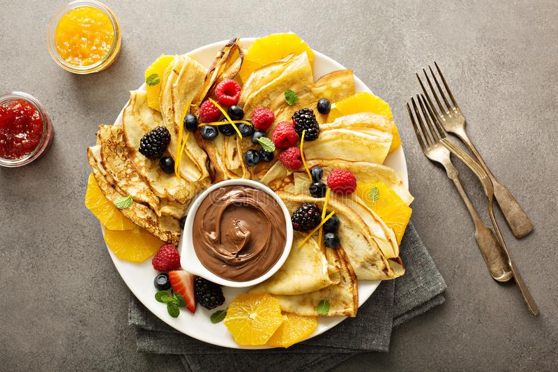 Thin crepes with fresh fruit and berries stock photo