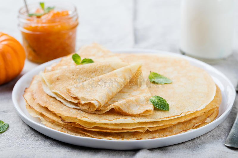 Thin crepes or pancakes with butter, honey and sour cream on a rustic textile background.  royalty free stock photography