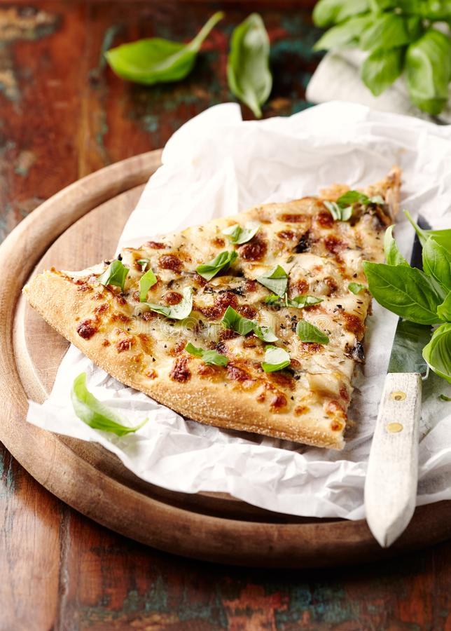 Thin-crust pizza topped with fresh basil leaves. Slice of pizza. Home made food. Italian vegetarian pizz. A. Concept for a tasty and hearty meal. Rustic wooden royalty free stock photos