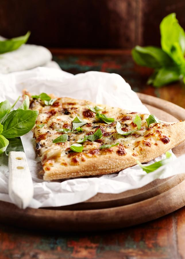 Thin-crust pizza topped with fresh basil leaves. Slice of pizza. Home made food. Italian vegetarian pizz. A. Concept for a tasty and hearty meal. Rustic wooden stock photo