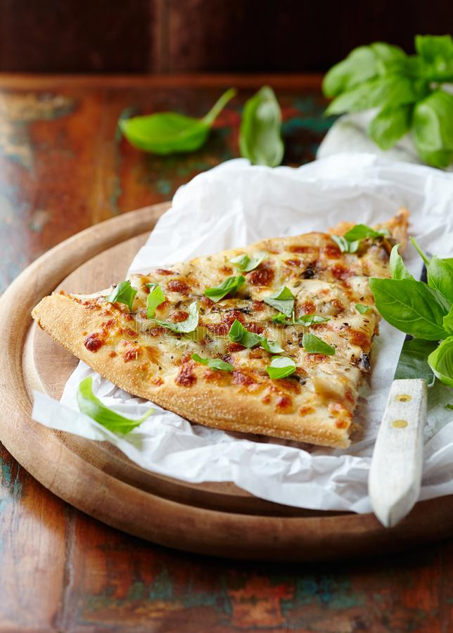 Thin-crust pizza topped with fresh basil leaves. Slice of pizza. Home made food. Italian vegetarian pizz. A. Concept for a tasty and hearty meal. Rustic wooden stock photography