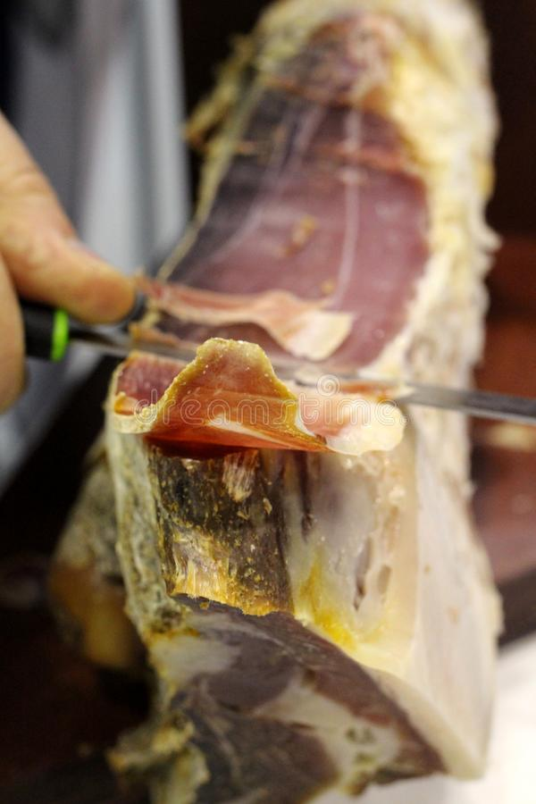 Thin cutting knife jerky ham traditional dish focus in the center royalty free stock image