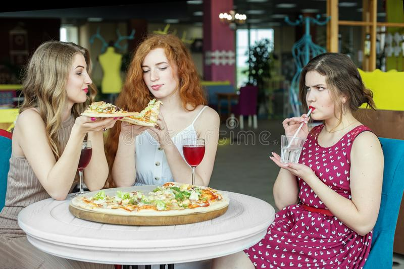 Thin girls eat pizza. The girl is on a diet.Concept for food, lifestyle and slimming royalty free stock images