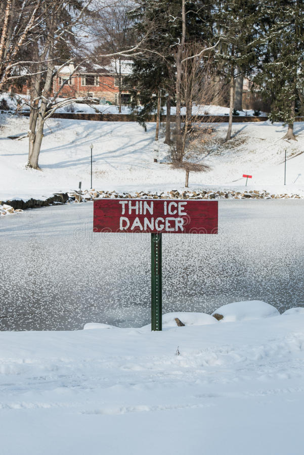 Thin ice danger. This thin ice danger sign sits in front of a pond of ice and duck feathers. Excellent use for the Thin Ice Danger sign royalty free stock image