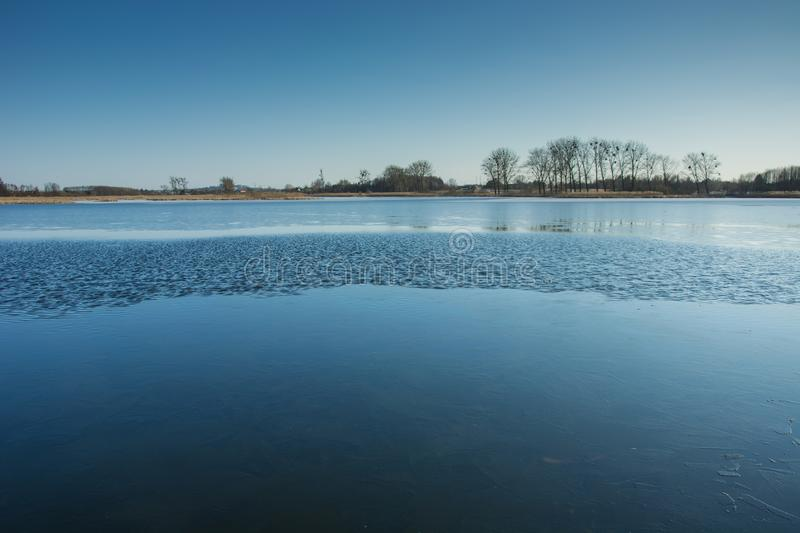 Thin ice and small waves on the lake. Trees on the shore and cloudless sky stock photo