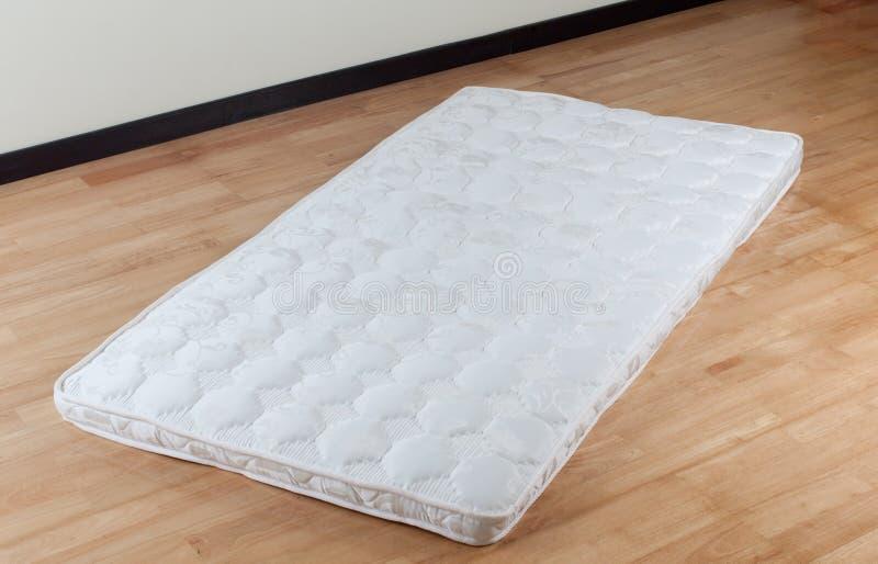 Thin mattress on wooden floor stock photo