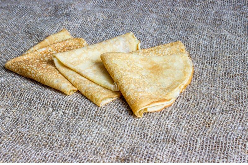 Thin Pancakes on a Sacking Background Top View. Fresh Homemade Crepes. Thin Pancakes on a Sacking Background Top View. Fresh Homemade Crepes Flat Lay stock photo