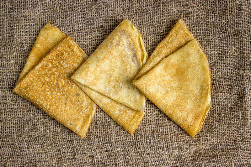 Thin Pancakes on a Sacking Background Top View. Fresh Homemade Crepes. Thin Pancakes on a Sacking Background Top View. Fresh Homemade Crepes Flat Lay royalty free stock photo