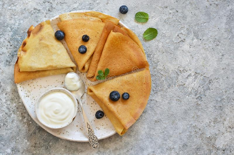 Thin pancakes with vanilla sauce, blueberry and mint on a cement background. View from above royalty free stock photo