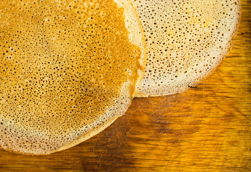 Thin Pancakes on a Wooden Background Top View. Fresh Homemade Porous Crepes Flat Lay royalty free stock photos