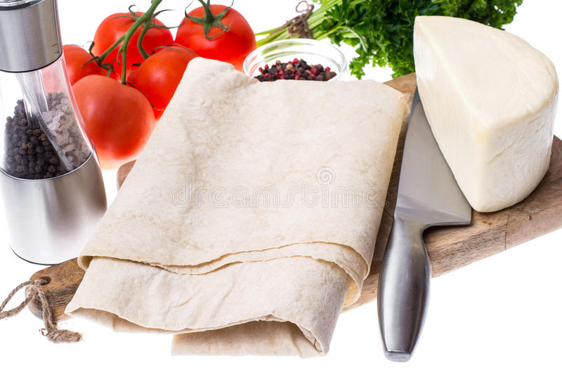 Thin pita bread, tomatoes, cheese and greens for making a light, hot breakfast royalty free stock photo
